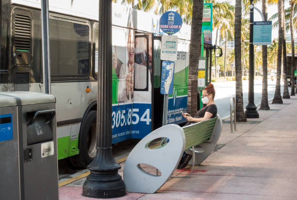 Woman at a bus stop wearing a face mask in Miami Beach stock photo