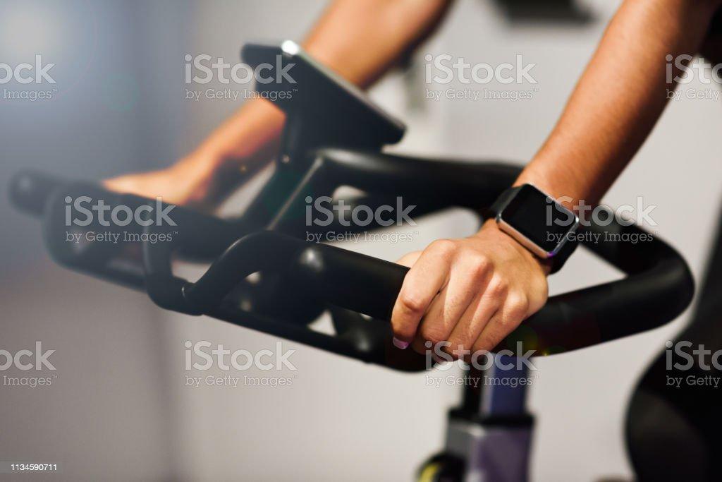 Vrouw op een sportschool doet Spinning of Cyclo indoor met Smart Watch - Royalty-free Actieve levenswijze Stockfoto
