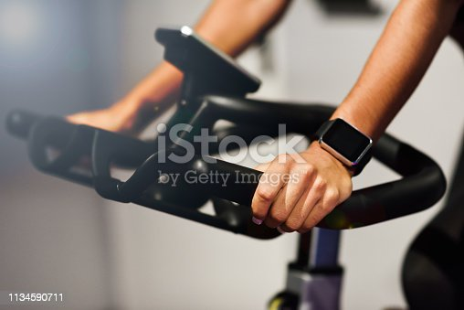 Hands of a woman training at a gym doing exercising or cyclo indoor with smart watch. Sports and fitness concept.