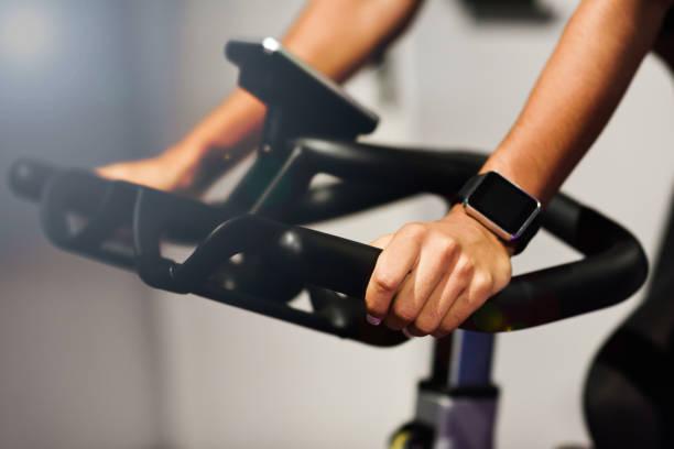 vrouw op een sportschool doet spinning of cyclo indoor met smart watch - ronddraaien stockfoto's en -beelden