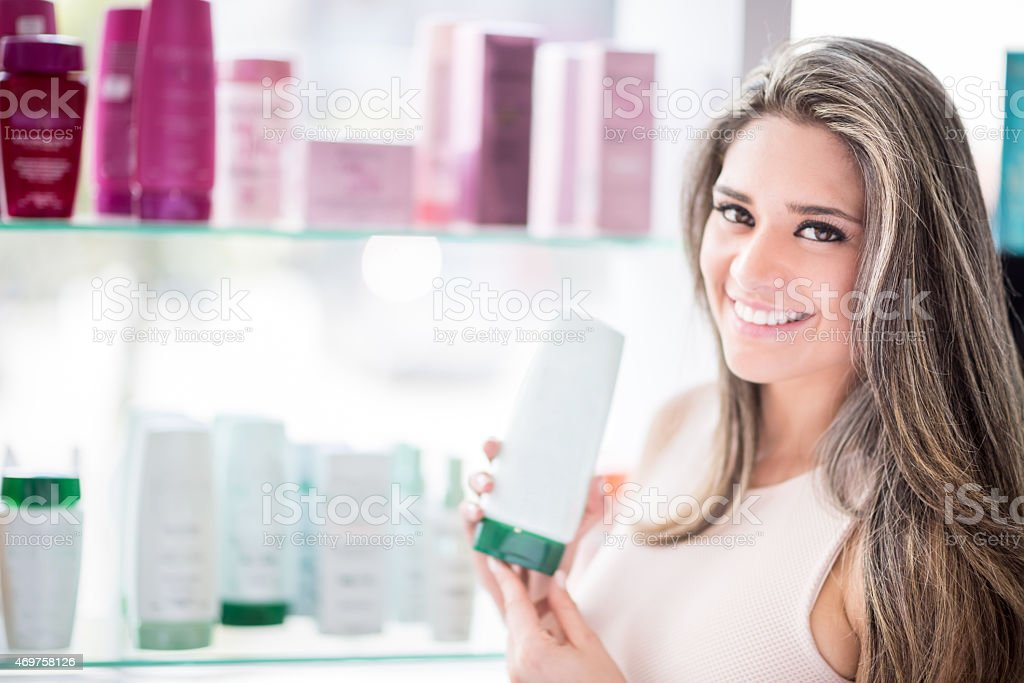 Beautiful woman at a hair salon holding beauty products