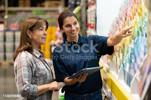 Woman at a home improvement store choosing paint colors and talking to the saleswoman about her options
