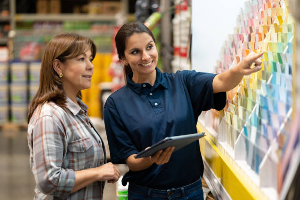 Woman at a home improvement store choosing paint colors Woman at a home improvement store choosing paint colors and talking to the saleswoman about her options sales clerk stock pictures, royalty-free photos & images