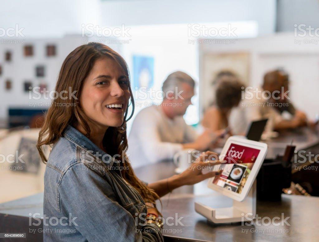 Vrouw in een restaurant kijken naar het menu op een tablet foto