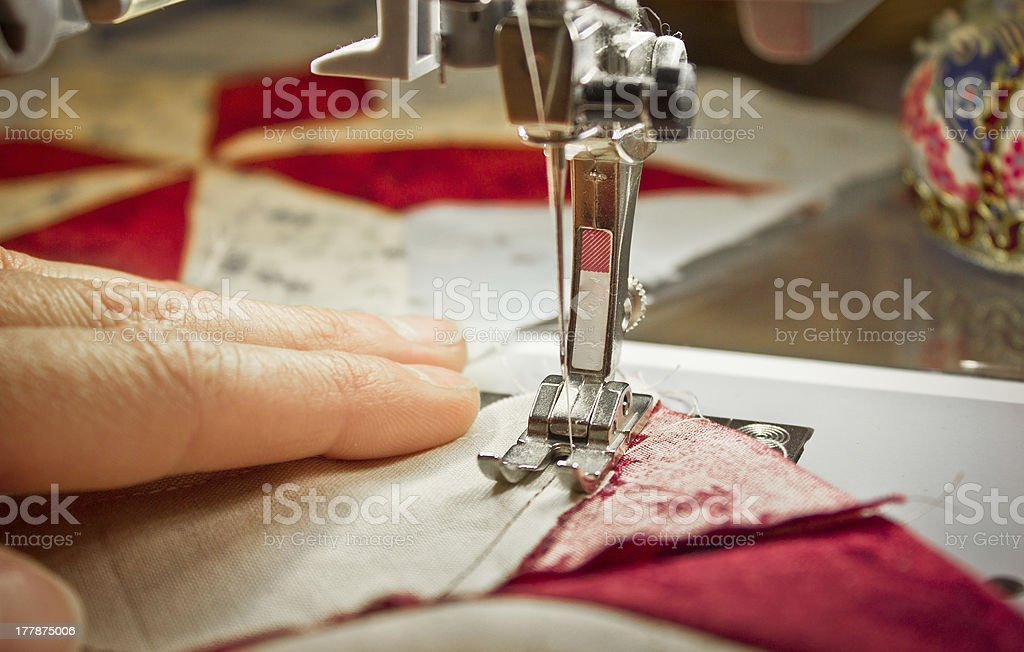 woman at a sewing machine closeup stock photo