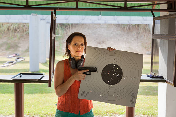 Woman at a shooting range with gun and target