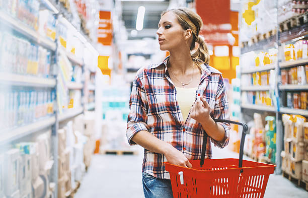 Woman at a supermarket. Closeup front view of an attractive blond woman walking between aisles at a local supermarket. She's carrying shopping cart and looking at products on the shelves, a bit uncertain of what she should buy. shopping basket stock pictures, royalty-free photos & images