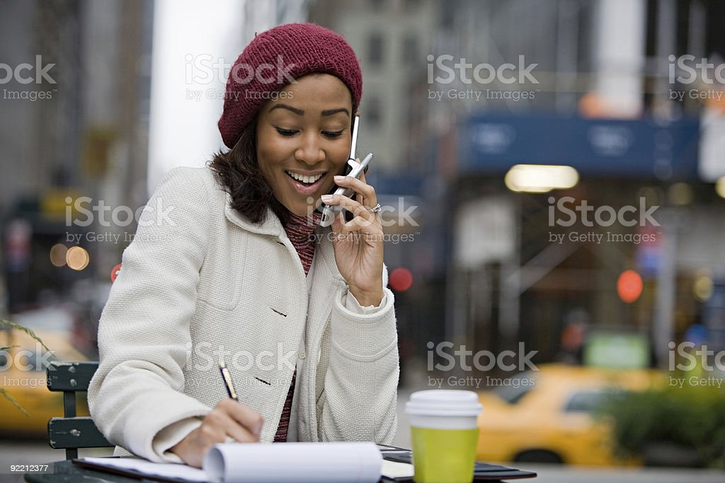 Woman at an outdoor cafe, chatting on her phone and writing royalty-free stock photo
