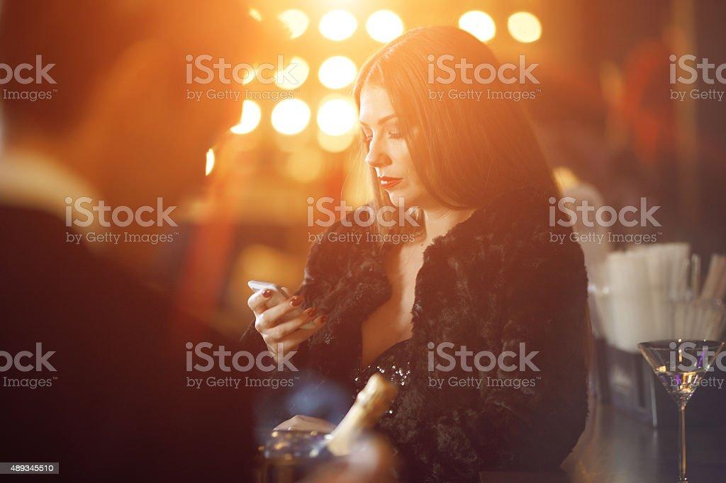 Woman at bar looking at cell phone stock photo