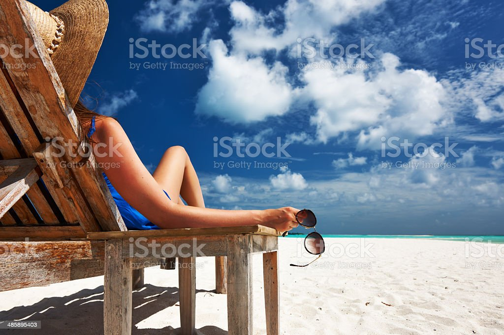 Woman at beach holding sunglasses stock photo