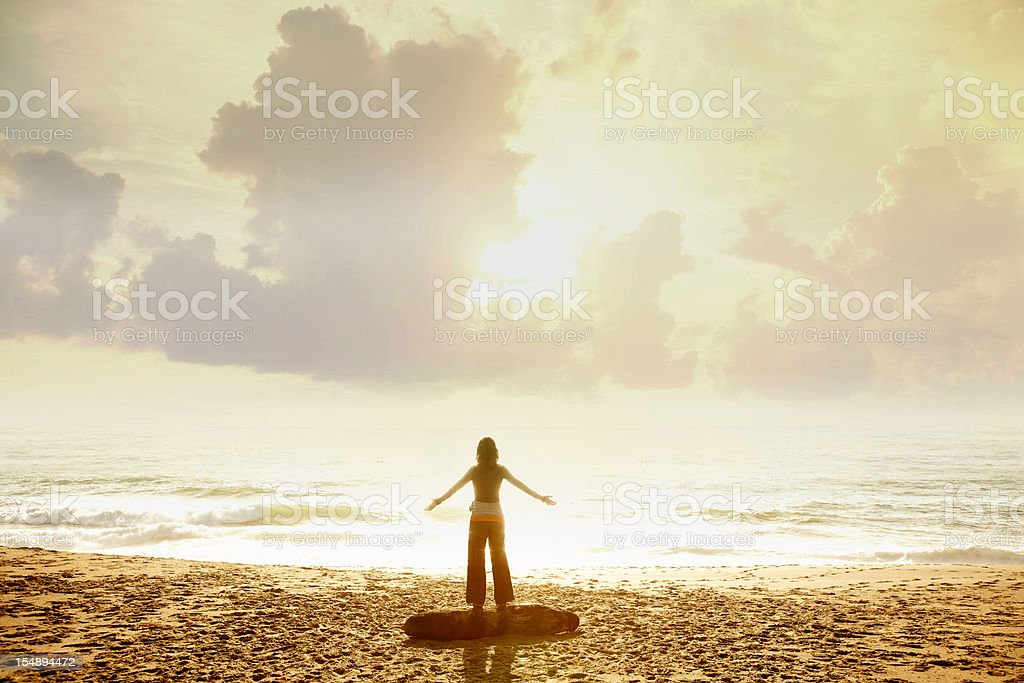 Woman at beach with arms extended stock photo