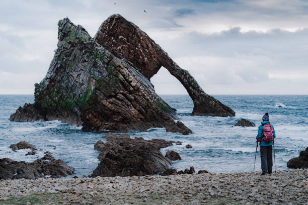 Woman at Bow Fiddle Rock, Portknockie, Scotland stock photo