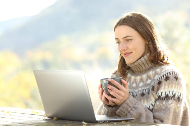 Woman at breakfast watching laptop content in winter stock photo