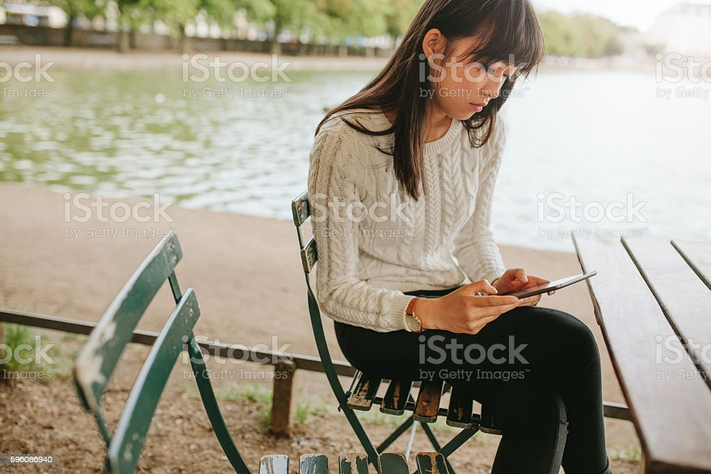 Woman at cafe by the pond using digital tablet royalty-free stock photo