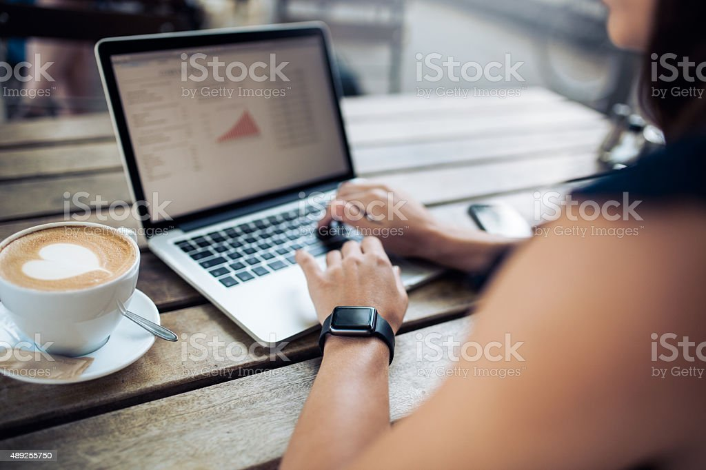 Woman at cafe working on her laptop stock photo