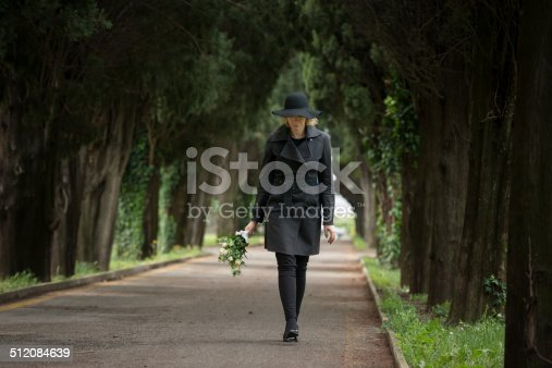 istock Woman at cemetery 512084639