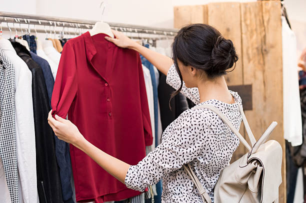 Woman at clothing store Woman choosing blouse from new collection of clothes in a boutique. Beautiful woman choosing clothes in a clothing shop. Rear view of girl doing shopping. blouse stock pictures, royalty-free photos & images