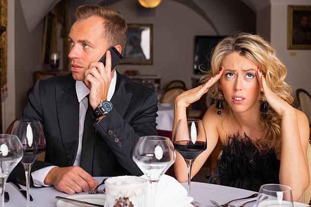 Woman at dinner date being annoyed Woman at dinner date being annoyed of man talking on the phone bad date stock pictures, royalty-free photos & images