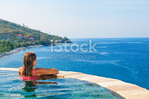 929671306 istock photo Woman at edge of infinity swimming pool with sea view. 1207099083