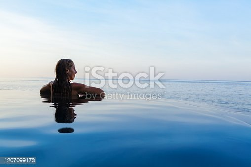 883117662 istock photo Woman at edge of infinity swimming pool with sea view. 1207099173