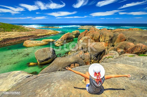 Happy woman looking the huge cracked elephant-shaped oval rocks of Elephant Rocks from promontory. Girl enjoying boulders of Great Southern Ocean in William Bay NP near Denmark, Western Australia.