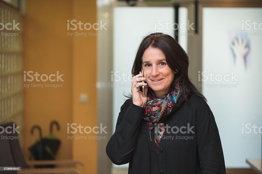 Frau im Eingangsbereich Arbeitsplatz, steht und redet mit Handy – Foto