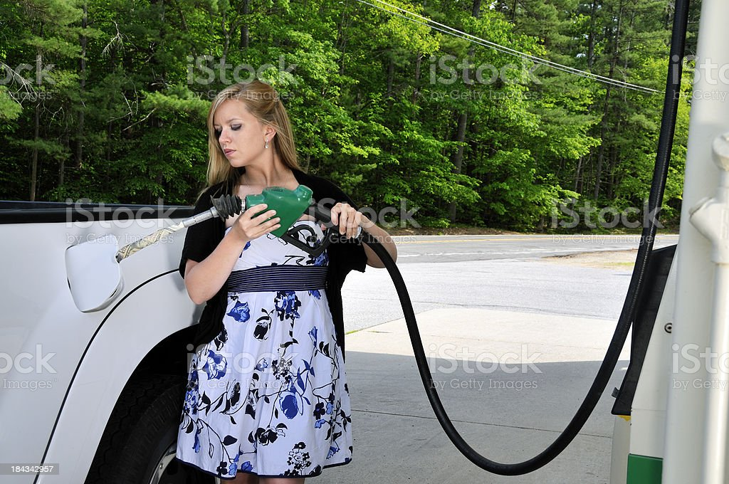 Woman at Gas Station Filling Truck with Money royalty-free stock photo