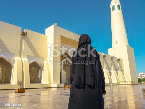 Back of woman with abaya dress looking the facade and high minaret of State Grand Mosque in Doha, Qatar, Middle East, Arabian Peninsula. Sunny day with blue sky. Muslim religion concept.