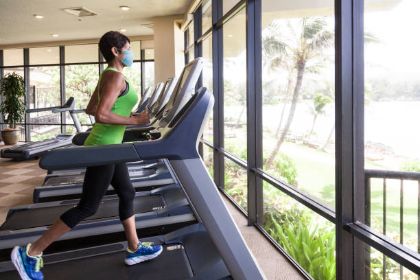 Woman at gym wearing mask to prevent spread of Covid-19 virus stock photo