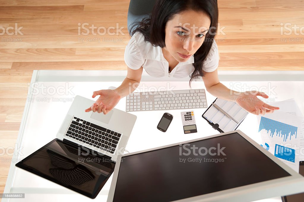 Woman at her desk looking frustrated royalty-free stock photo