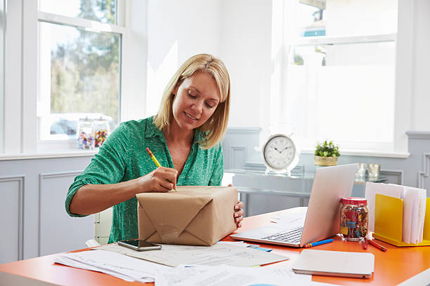 Woman At Home Addressing Package For Mailing stock photo