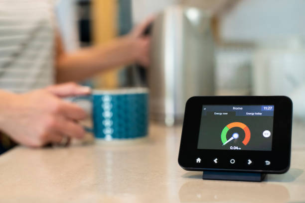 frau zu hause kochen wasserkocher für heißgetränk mit smart energy meter im vordergrund - messgerät stock-fotos und bilder