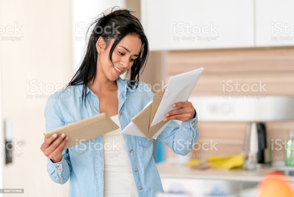 Woman at home checking her mail stock photo