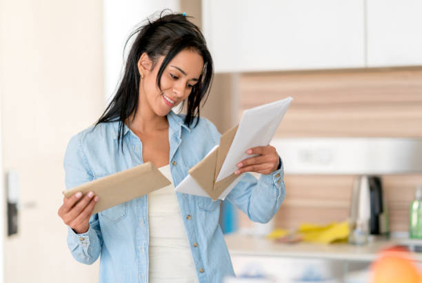 woman at home checking her mail - mail stock photos and pictures