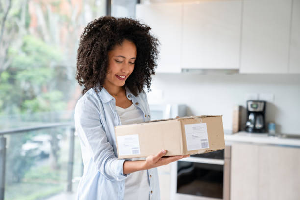 Woman at home getting a parcel in the mail Happy African American woman at home getting a parcel in the mail and smiling - lifestyle concepts clothes in box stock pictures, royalty-free photos & images