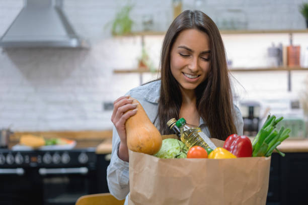 woman at home getting groceries out of a shopping bag - grocery home foto e immagini stock