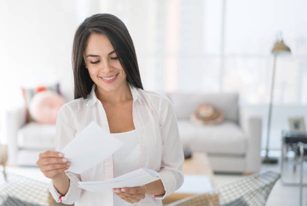 woman at home getting the mail - mail stock photos and pictures