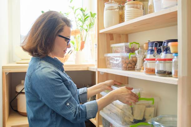 Mujer en casa en la cocina, cerca de estantes de madera con comida - foto de stock
