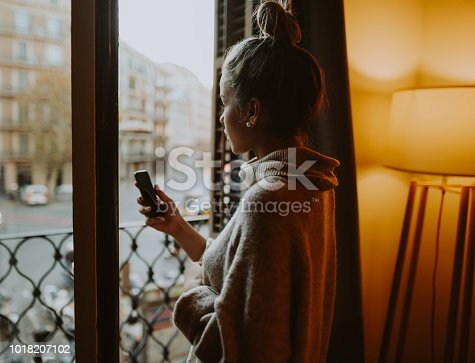 Beautiful woman at home using smartphone