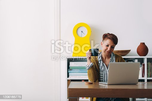 happy woman sitting desk and using laptop in her home