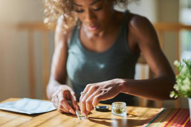 여자 집에서 대마초를 구입 하는 약국에서 마리화나의 공동를 롤링 - 굴리기 뉴스 사진 이미지