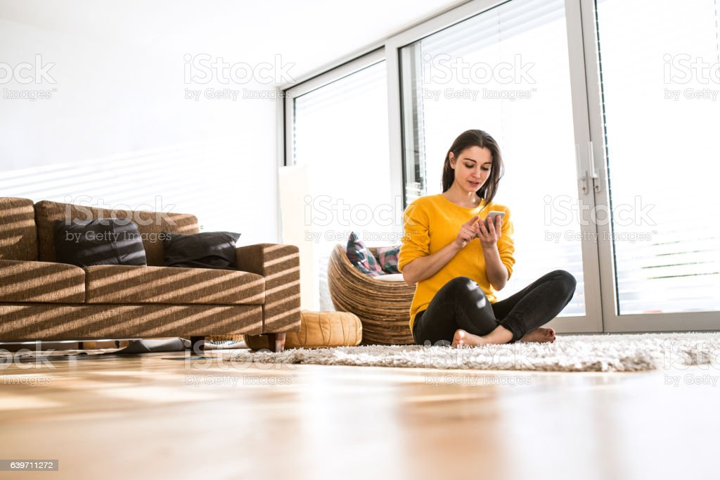 woman at home sitting on carpet holding smart phone texting stock rh istockphoto com woman at home smoked salmon pate recipe woman at home subscription