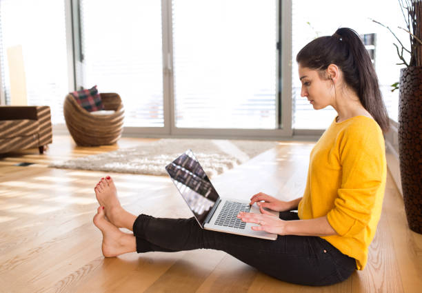 Woman at home sitting on the floor, working on laptop – Foto
