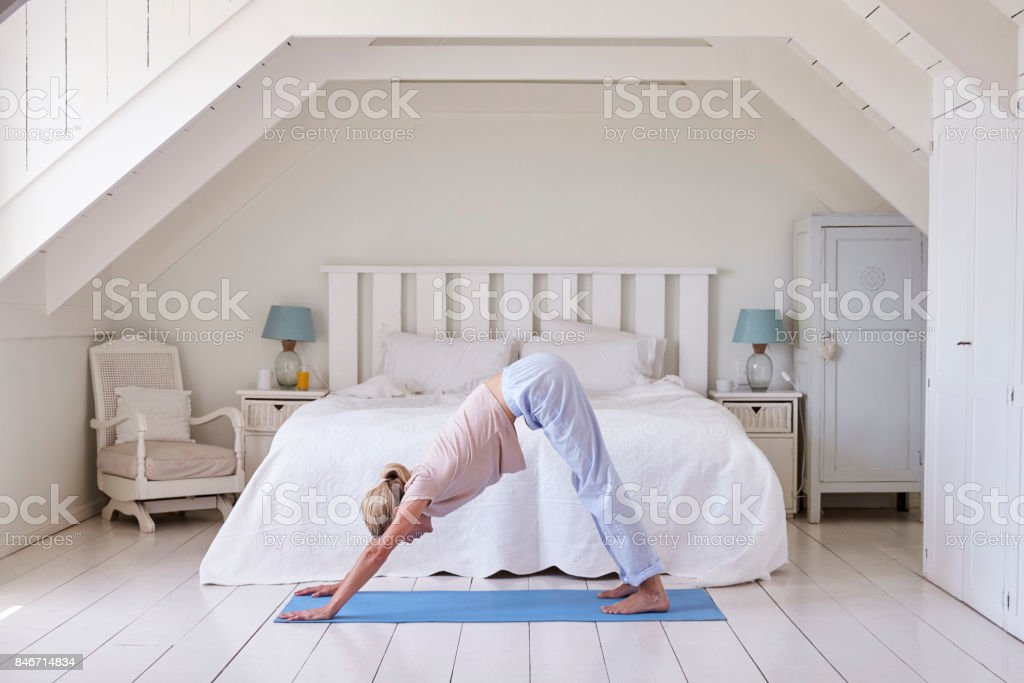 Woman At Home Starting Morning With Yoga Exercises In Bedroom Stock