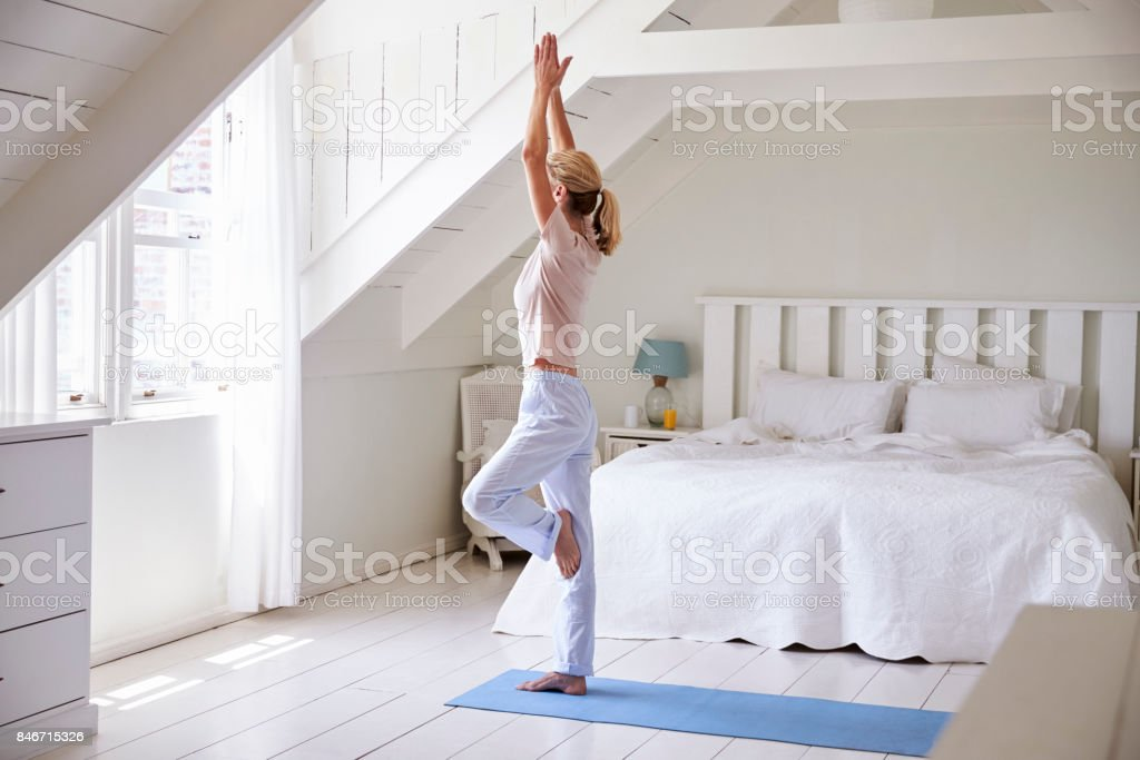 Woman At Home Starting Morning With Yoga Exercises In Bedroom stock photo