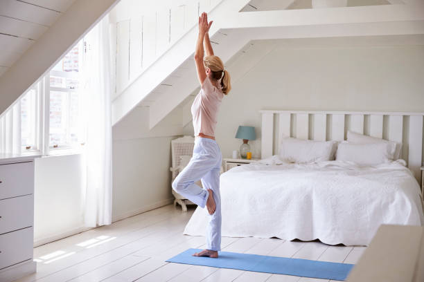 woman at home starting morning with yoga exercises in bedroom - routine foto e immagini stock