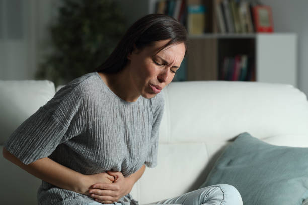 Woman at home suffering belly ache in the night stock photo