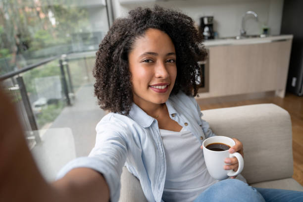 vrouw thuis die een selfie neemt terwijl het drinken van koffie - selfie stockfoto's en -beelden