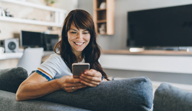 Woman at home texting on phone Young bautiful woman texting surfing the net on the sofa at home one mid adult woman only stock pictures, royalty-free photos & images