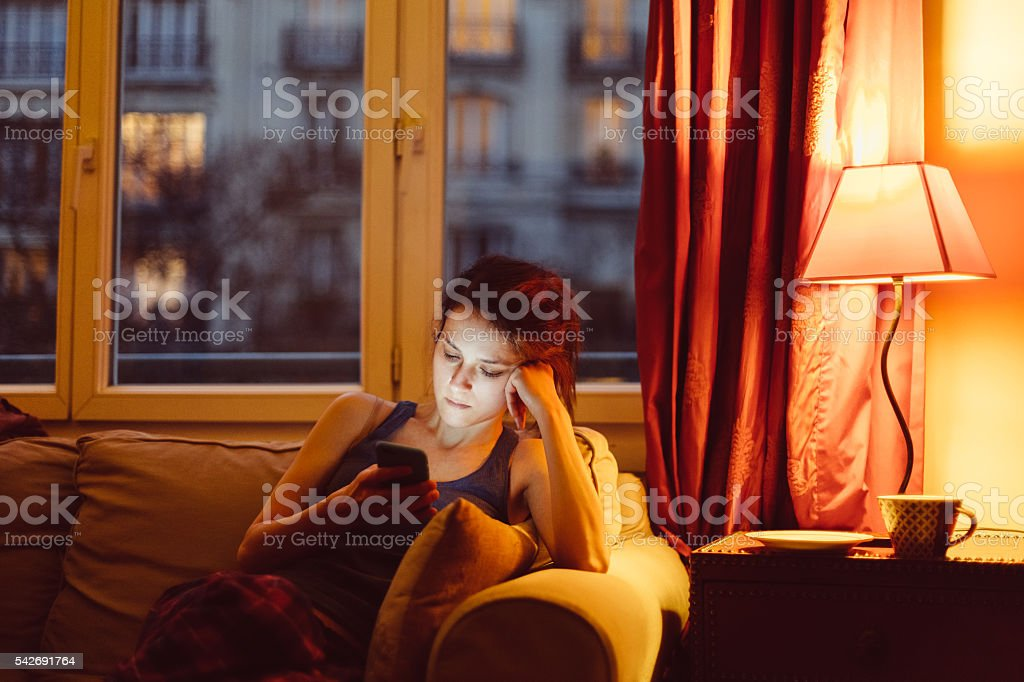Woman at home texting on phone stock photo